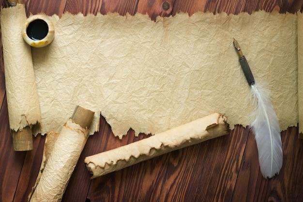 Papel antiguo, pergamino y pluma sobre papel de madera con espacio de copia