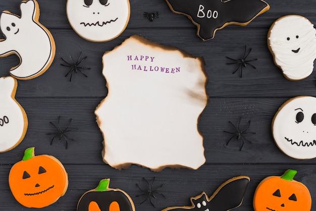 Papel ardiente entre pan de jengibre de halloween y arañas decoradoras