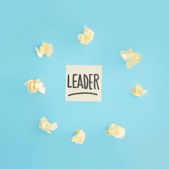 Papel arrugado amarillo rodeado alrededor de nota adhesiva del texto del líder en el contexto azul