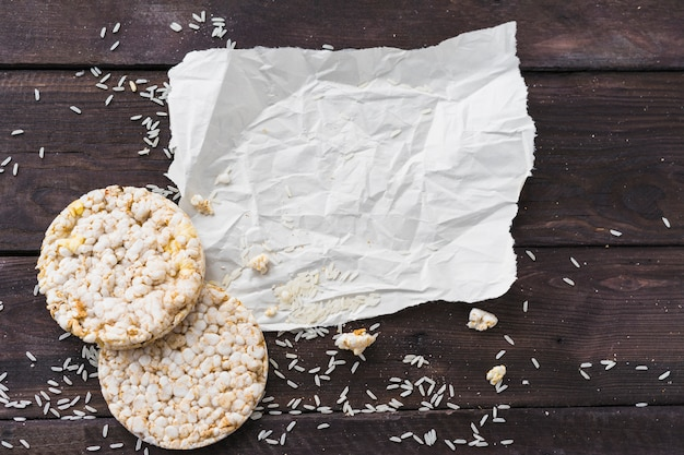 Papel arrugado con dos pasteles redondos de arroz inflado con granos en el escritorio de madera