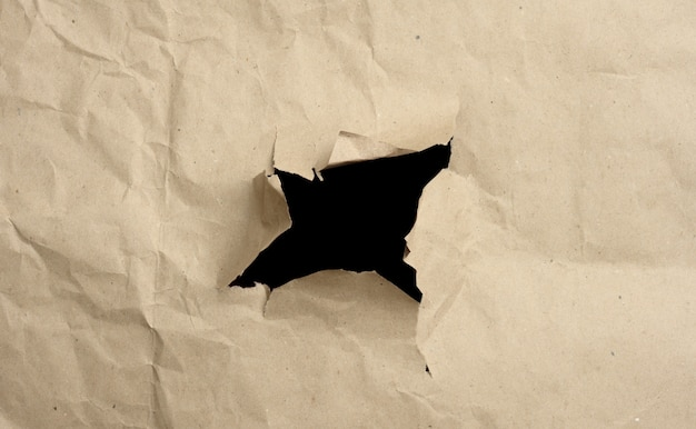 Papel arrugado marrón con un agujero, bordes rasgados y curvados. superficie abstracta