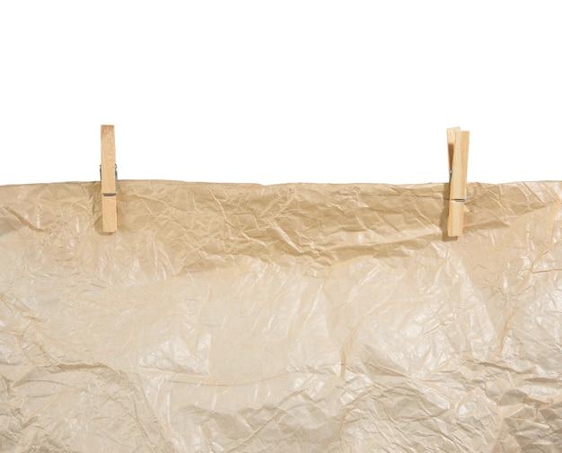 Papel arrugado marrón colgando de pinzas para la ropa de madera, textura aislada sobre superficie blanca