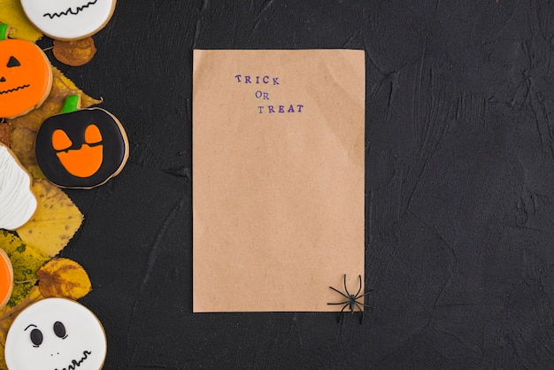 Papel artesanal con araña cerca de pan de jengibre y follaje