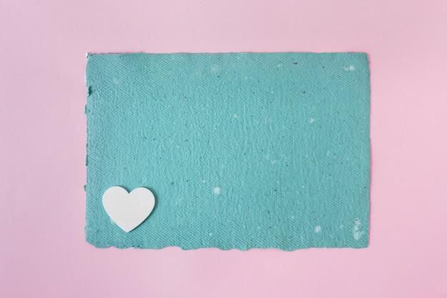 Papel artesanal azul y adorno de corazón.