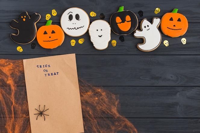 Papel artesanal en tela de araña cerca de pan de jengibre y cráneos decorativos