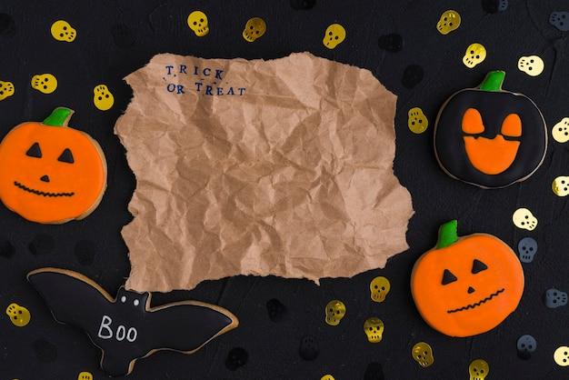 Papel artesanal entre galletas de halloween y cráneos ornamentales
