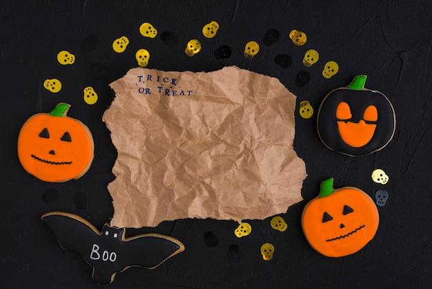 Papel artesanal entre pan de jengibre de halloween y cráneos decorativos