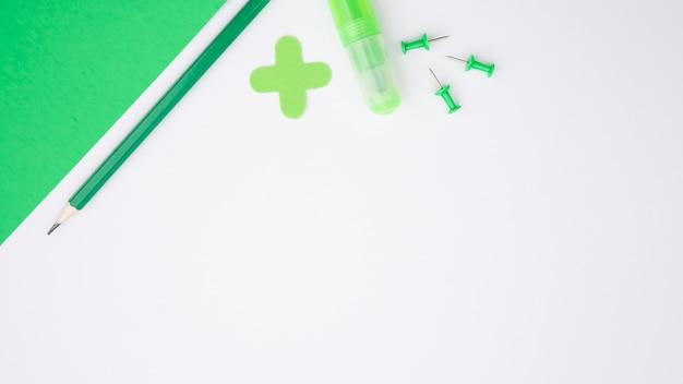 Papel artesanal verde; lápiz; pegamento y alfiler sobre superficie blanca