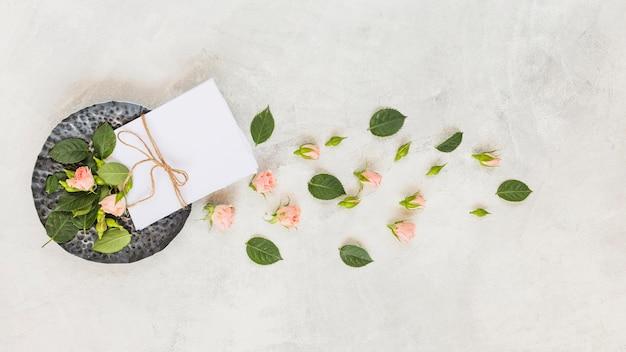 Papel atado con una cuerda; flores rosadas y hojas sobre fondo concreto