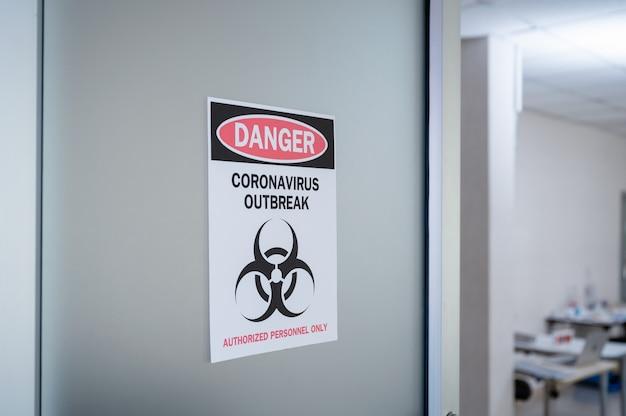 Papel de aviso de alerta en la puerta de peligro brote de coronavirus con símbolo de riesgo biológico y personal autorizado únicamente