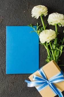 Papel azul en blanco, caja de regalo y ramo de flores blancas