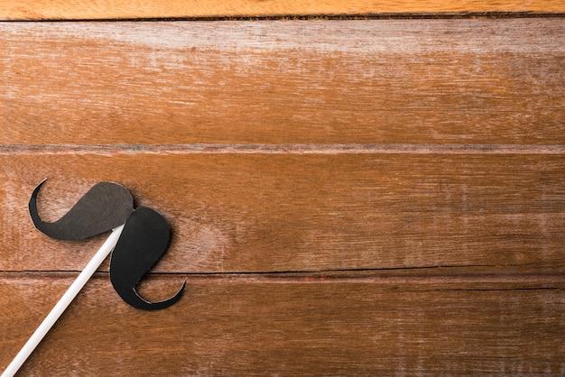 Papel de bigote negro sobre fondo de madera