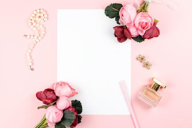 Papel blanco en blanco, bolígrafo, joyas, perfumes, flores sobre fondo pastel