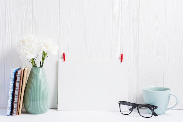 Papel blanco en blanco con clavija de ropa roja; los anteojos; vaso; florero y libros sobre fondo de textura de madera.