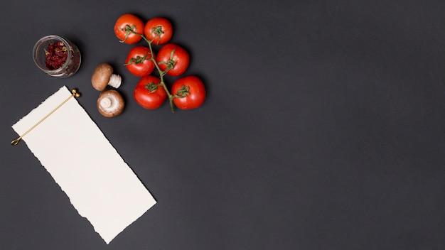 Papel blanco en blanco para escribir una receta y un ingrediente sabroso en la parte superior de la cocina