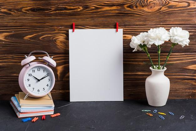 Papel blanco en blanco; florero; despertador y cuadernos contra fondo de madera.