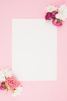 Papel blanco en blanco con flores frescas sobre fondo rosa