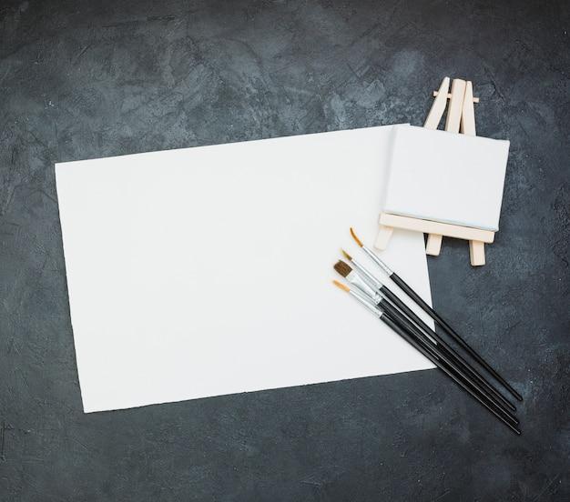 Papel blanco en blanco con mini caballete y pincel sobre fondo de pizarra