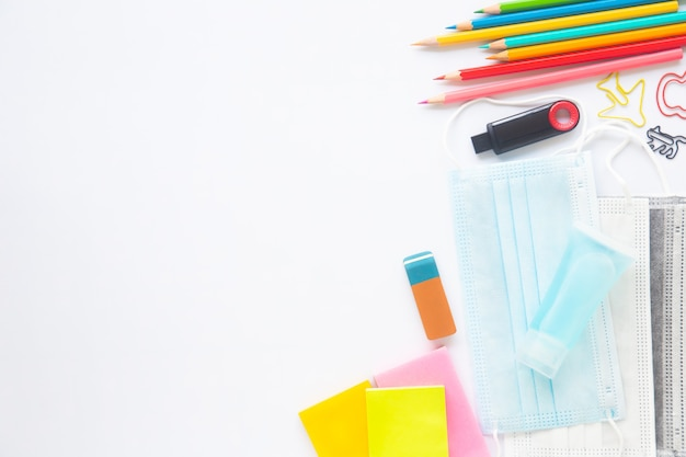 Papel blanco en blanco o cuaderno con papelería, mascarilla y desinfectante de manos sobre fondo blanco.