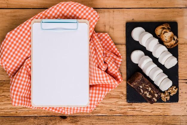 Papel blanco en blanco en el portapapeles con mantel cerca de queso de cabra y bocadillo sobre piedra de pizarra