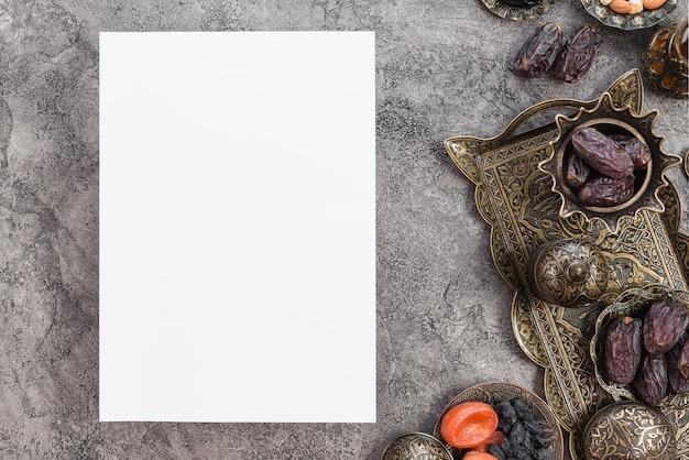 Papel blanco en blanco de ramadan kareem con fechas premium y frutas secas en el fondo