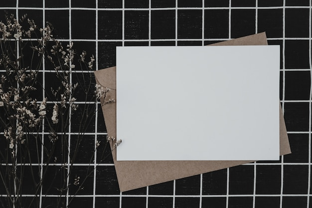 Papel blanco en blanco sobre papel marrón con flor seca de limonium y caja de cartón sobre tela negra con patrón de cuadrícula en blanco y negro. maqueta de tarjeta de felicitación en blanco horizontal.