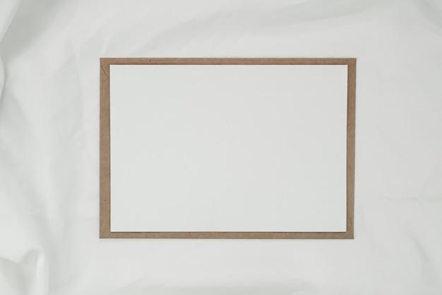 Papel blanco en blanco sobre papel marrón con tela blanca. tarjeta de felicitación en blanco horizontal. vista superior del sobre de artesanía sobre fondo blanco.