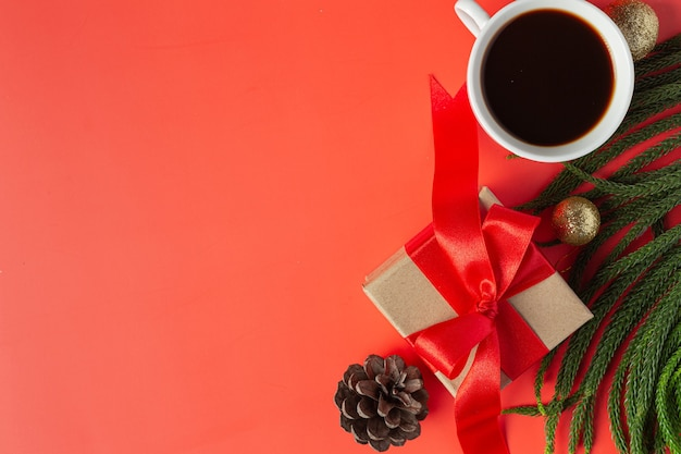 Un papel blanco en blanco, una taza de café y una caja de regalo en el piso rojo