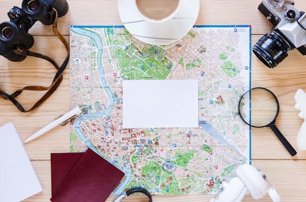 Papel blanco en blanco; taza de té y varios accesorios de viajero sobre fondo de madera.