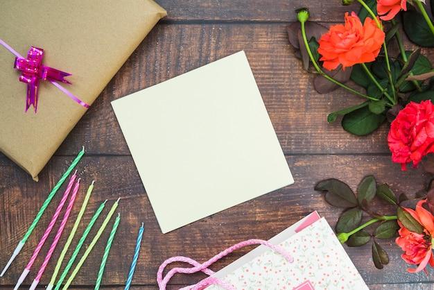 Papel en blanco blanco con velas; caja de regalo; flores y bolso de compras en la mesa
