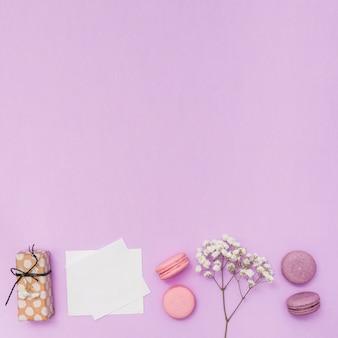Papel en blanco con caja de regalo y rama de flores