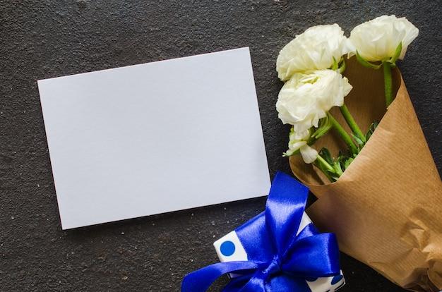 Papel en blanco, caja de regalo y ramo de flores blancas