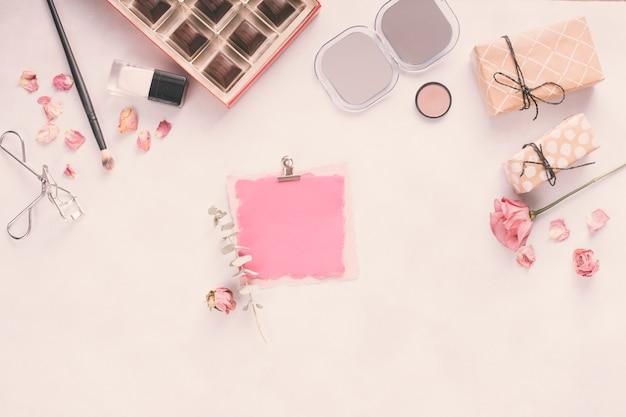 Papel en blanco con cajas de regalo, rosas y cosméticos.
