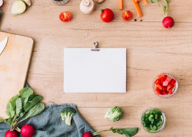 Papel en blanco con clip de papel rodeado de verduras en mesa de madera