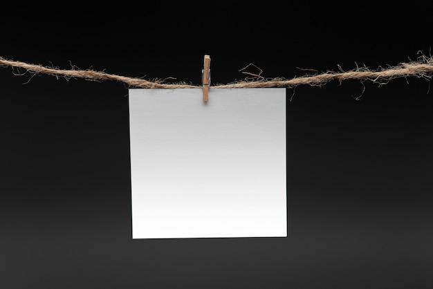 Papel en blanco, colgando de la cuerda por pin