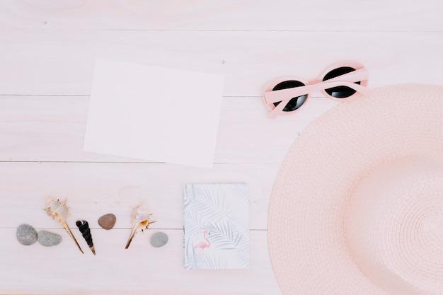 Papel en blanco y cosas de verano en superficie ligera.