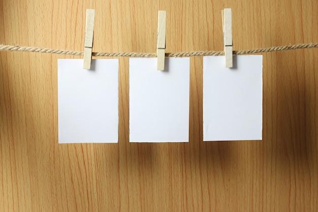 El papel en blanco cuelga en la cuerda marrón.