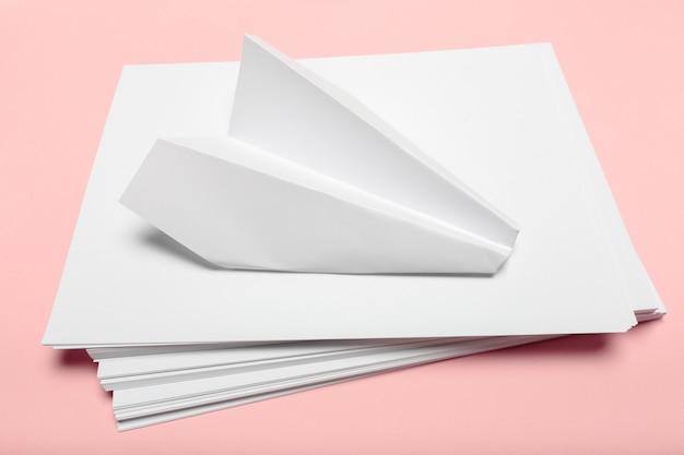 Papel en blanco encima de escritorio rosa pastel