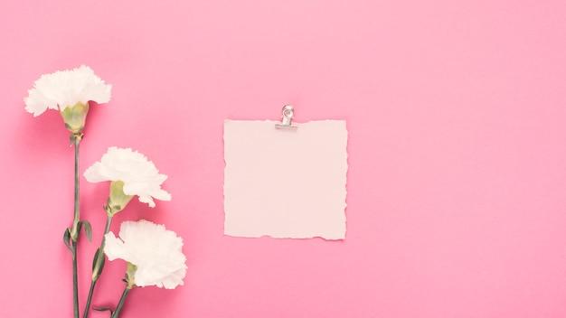 Papel en blanco con flores blancas en mesa