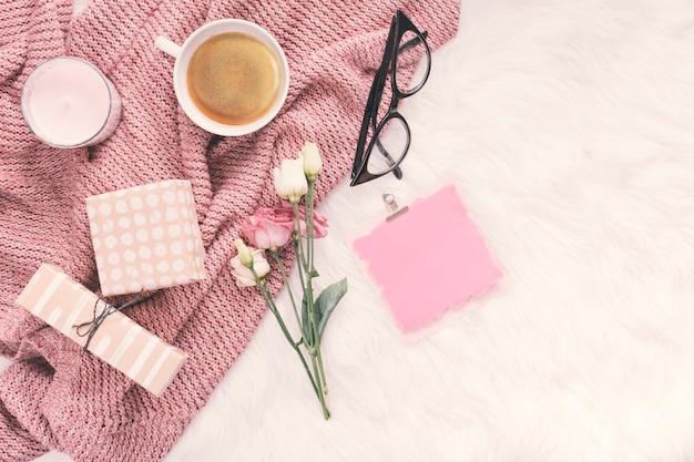 Papel en blanco con flores, cajas de regalo y taza de café.