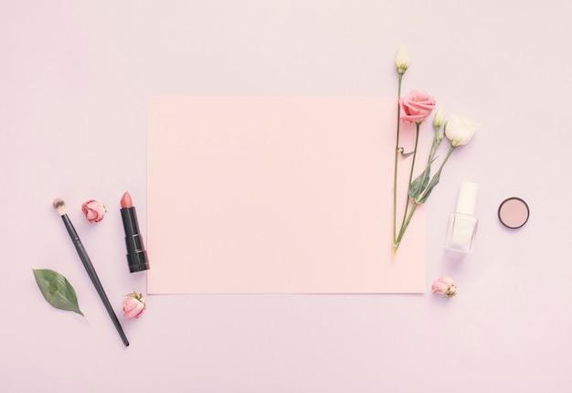 Papel en blanco con flores, esmalte de uñas y lápiz labial en la mesa
