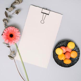 Papel en blanco con flores y galletas en la mesa