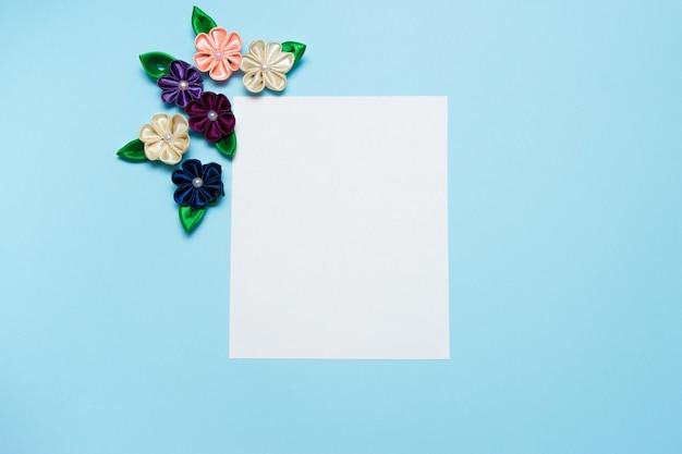 Papel en blanco con flores de satén y copia espacio sobre un fondo azul.