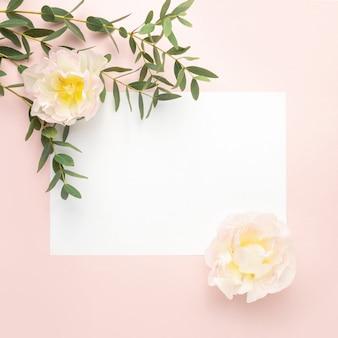 Papel en blanco, flores de tulipán, ramas de eucalipto sobre fondo rosa pastel