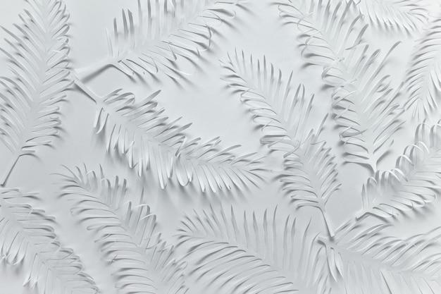 Papel blanco hecho patrón con hojas tropicales