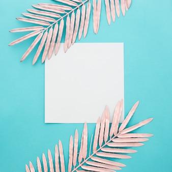 Papel en blanco con hojas de color rosa sobre fondo azul
