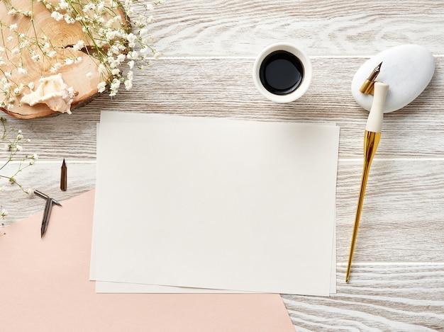 Papel en blanco para invitación o carta sobre fondo blanco de madera con pluma y tinta de caligrafía. vista desde arriba.