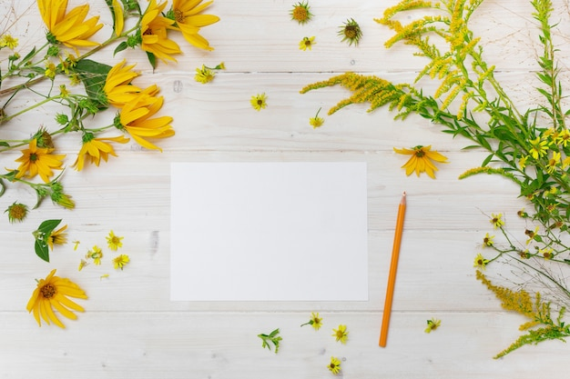 Un papel en blanco junto a un lápiz amarillo sobre una superficie de madera con flores de pétalos amarillos