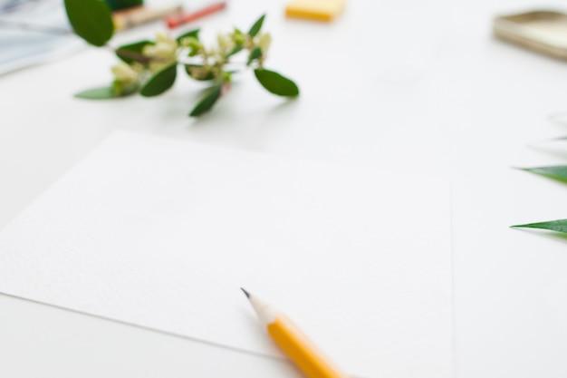 Papel en blanco con lápiz y flores.