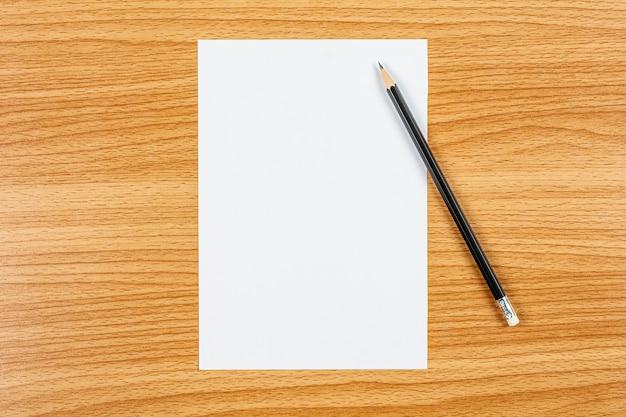 Papel en blanco y un lápiz sobre el escritorio de madera. - espacio en blanco para texto publicitario.